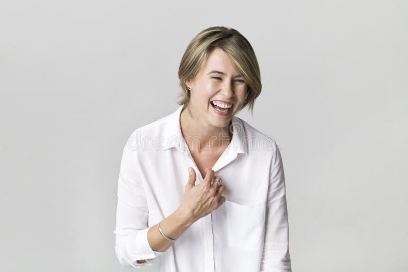 Uśmiechnięta pozytywna kobieta z atrakcyjnym spojrzeniem, jest ubranym białego eleg zdjęcia stock
