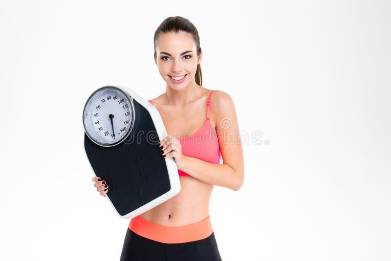 Uśmiechnięta pozytywna młoda sprawności fizycznej kobieta w sportwear mieniu waży skala fotografia royalty free