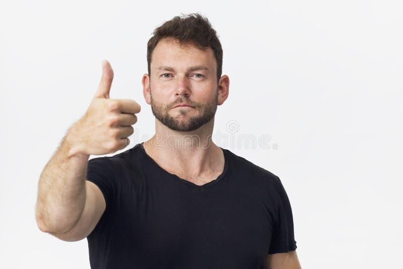 Uśmiechnięta pozytywna samiec z atrakcyjnym spojrzeniem, będący ubranym czarną koszulkę, pozuje przeciw białej pustej ścianie zdjęcia stock