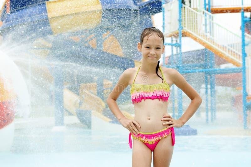 Uśmiechnięta preteen dziewczyny pozycja pod wodnymi kroplami Zamazany waterpa fotografia royalty free