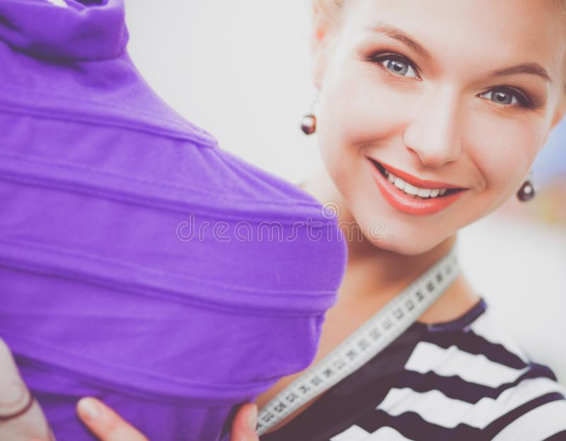 Uśmiechnięta projektant mody kobieta stoi blisko mannequin w biurze obraz stock