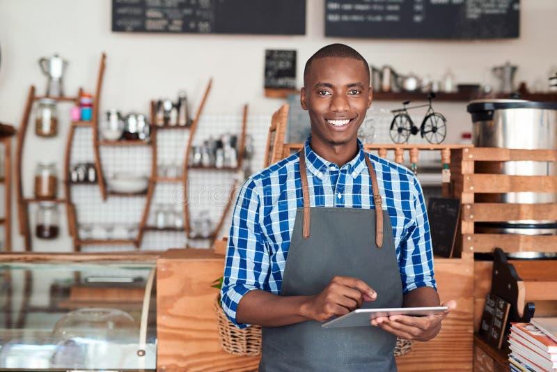 Uśmiechnięta przedsiębiorca pozycja w jego kawiarni używać cyfrową pastylkę obrazy royalty free