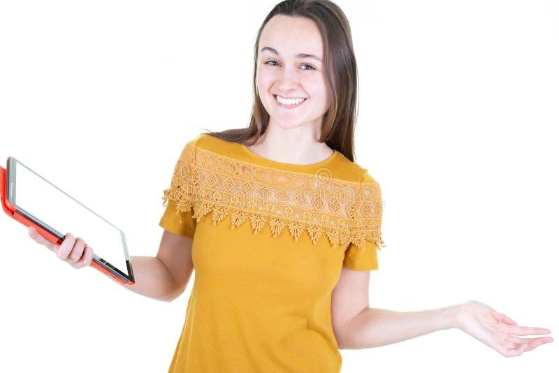 Uśmiechnięta przypadkowa kobieta używa jej pastylka komputer osobistego odizolowywającego na białym tle obrazy stock