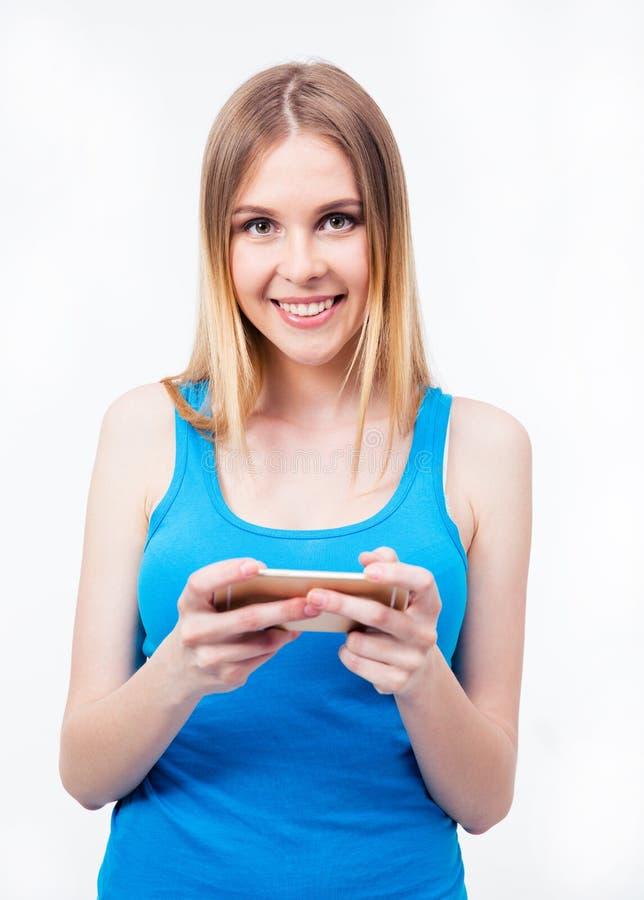 Uśmiechnięta przypadkowa kobieta używa smartphone zdjęcia stock