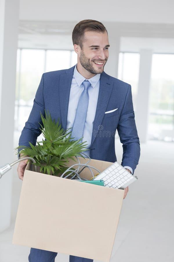 Uśmiechnięta przystojna młoda biznesmen pozycja z kartonem w nowym biurze obrazy stock