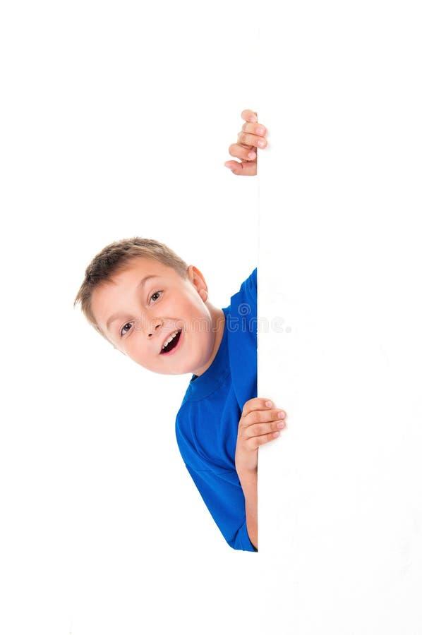 Uśmiechnięta przystojna nastolatek chłopiec jest ubranym jaskrawą błękitną koszulkę i pozuje za białym panelem odizolowywającym n obraz royalty free