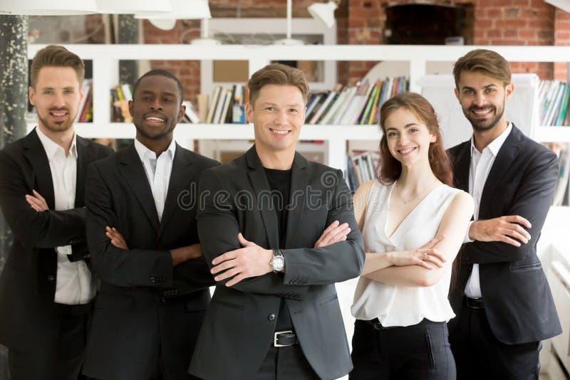 Uśmiechnięta różnorodna drużyna pozuje z rękami krzyżować obrazy royalty free