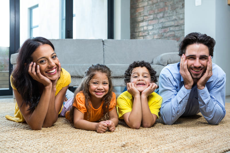 Uśmiechnięta rodzina na dywanie w żywym pokoju obraz stock