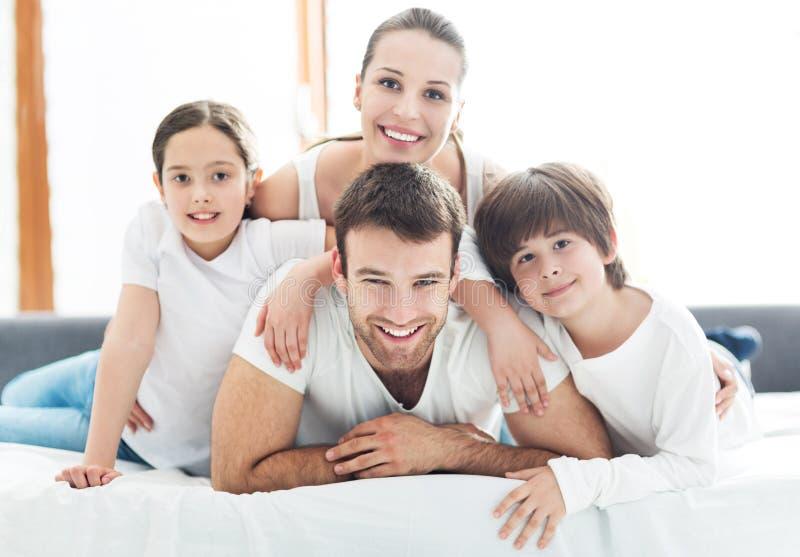 Uśmiechnięta rodzina w łóżku fotografia stock