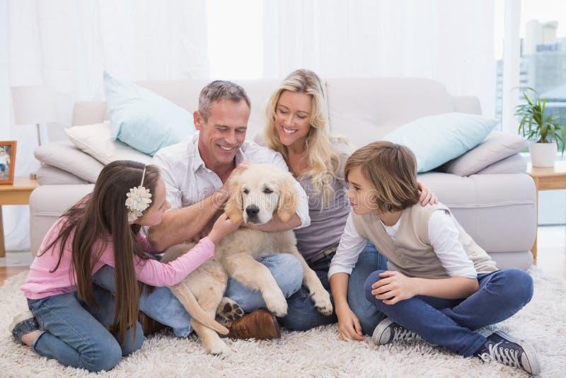 Uśmiechnięta rodzina z ich zwierzę domowe żółtym labradorem na dywaniku obraz stock