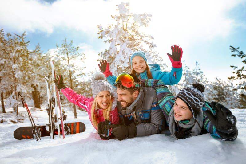 Uśmiechnięta rodzinna cieszy się zima być na wakacjach w górach na śniegu obrazy royalty free