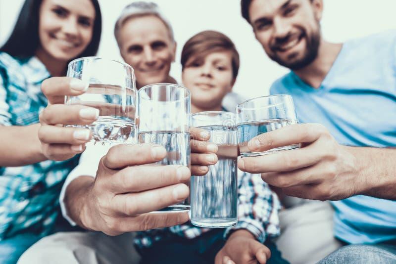 Uśmiechnięta Rodzinna woda pitna w szkłach w domu zdjęcie stock
