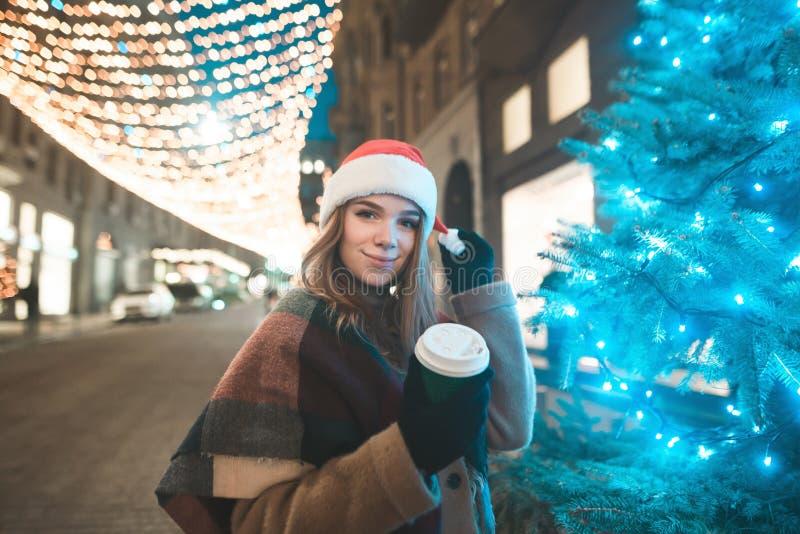 Uśmiechnięta słodka dziewczyna w Bożenarodzeniowym kapeluszu i filiżanka kawy w jej ręka stojakach przy zdjęcia royalty free