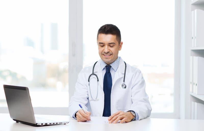 Uśmiechnięta samiec lekarka z laptopem w medycznym biurze obrazy royalty free