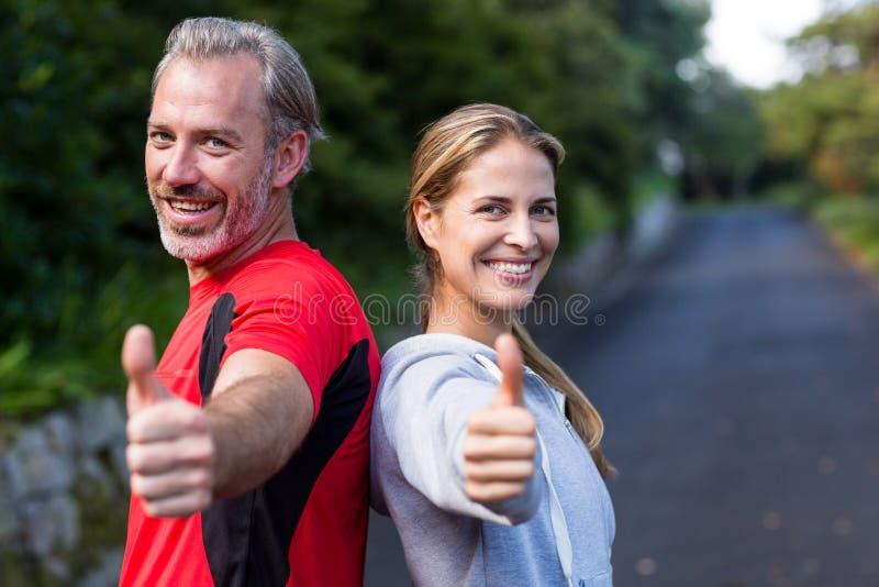 Uśmiechnięta sportowa para pokazuje aprobaty zdjęcie stock