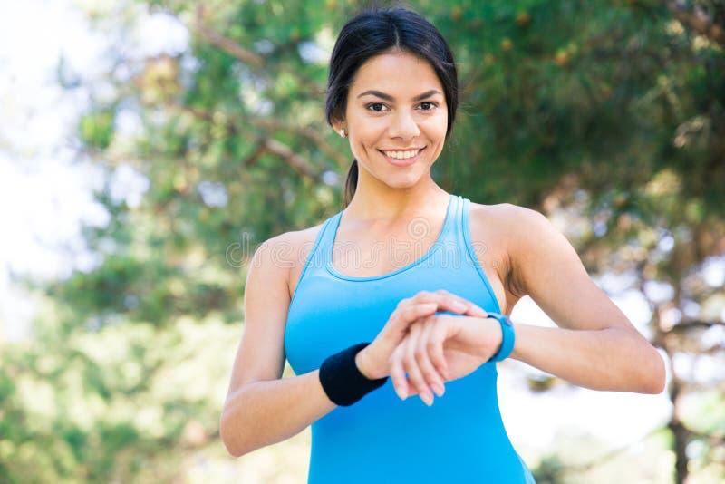 Uśmiechnięta sporty kobieta używa mądrze zegarek outdoors obrazy stock