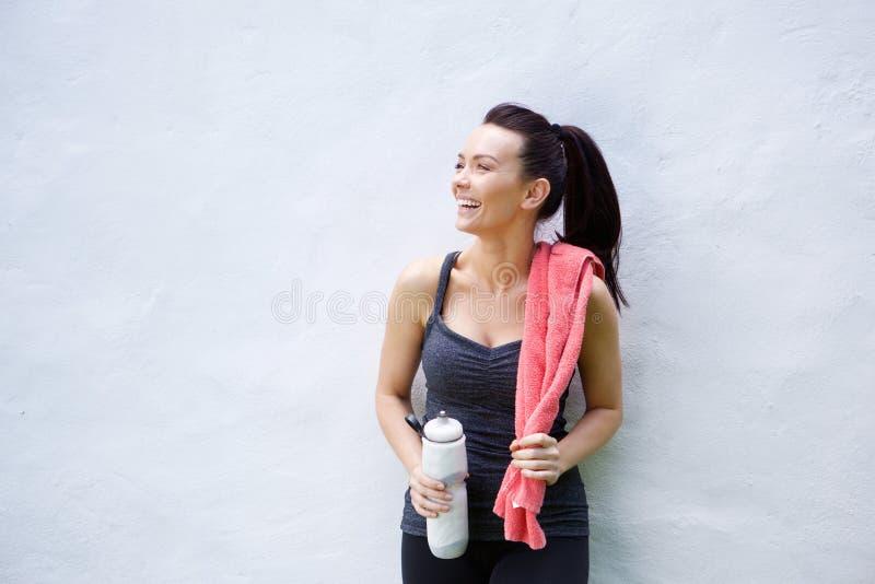Uśmiechnięta sporty kobieta z bidonem i ręcznikiem obrazy royalty free