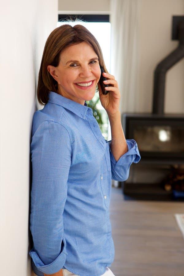 Uśmiechnięta stara kobieta opowiada na telefonie komórkowym i domu zdjęcie royalty free