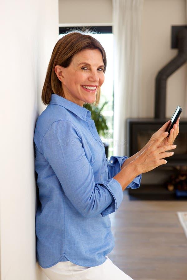 Uśmiechnięta stara kobieta używa telefon komórkowego i dom obrazy royalty free