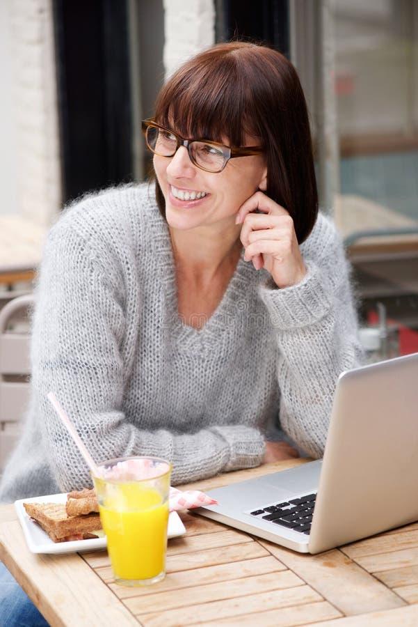 Uśmiechnięta stara kobieta z laptopem przy kawiarnią obrazy royalty free