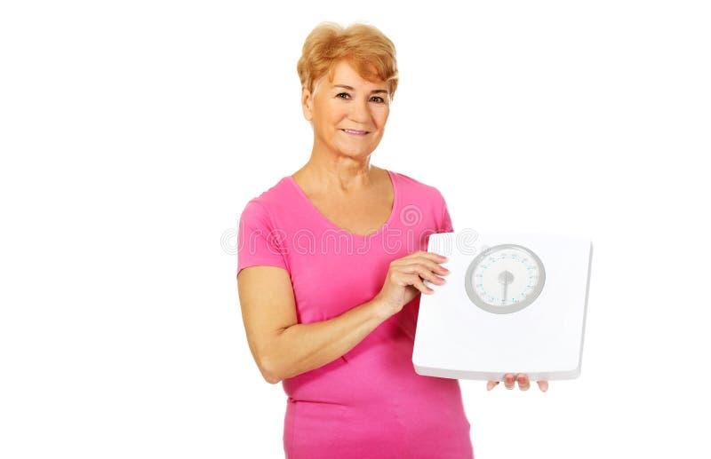 Uśmiechnięta starej kobiety mienia ciężaru skala fotografia stock
