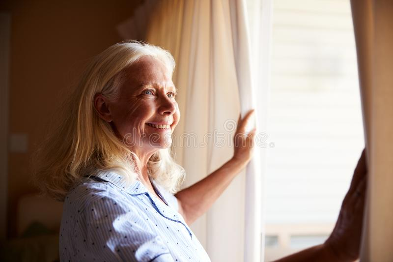 Uśmiechnięta starsza biała kobieta otwiera zasłony na pogodnym ranku, boczny widok, zakończenie w górę fotografia royalty free
