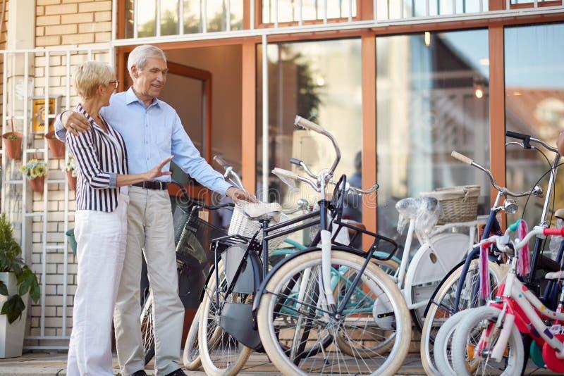 Uśmiechnięta starsza kobieta i mężczyzna kupuje nowego bicykl w sklepie fotografia royalty free