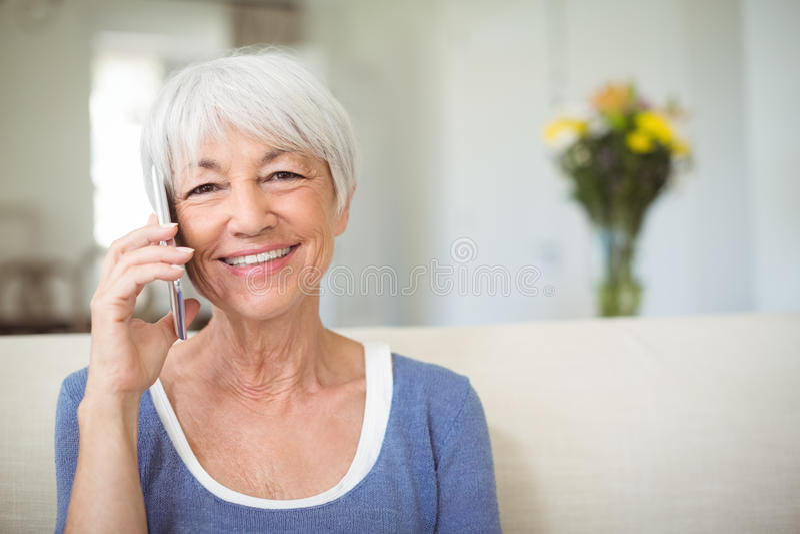 Uśmiechnięta starsza kobieta opowiada na telefonie komórkowym w żywym pokoju obrazy royalty free