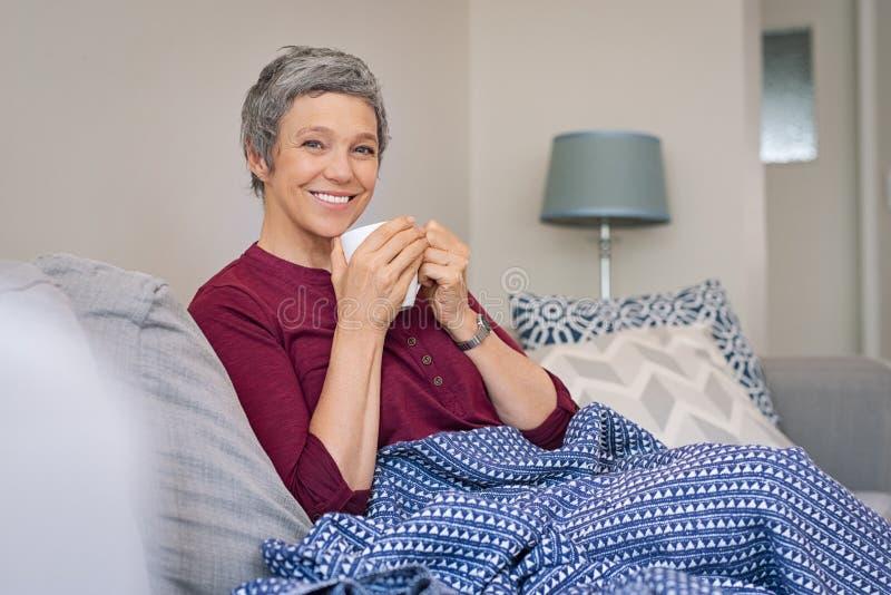 Uśmiechnięta starsza kobieta pije kawę obrazy stock