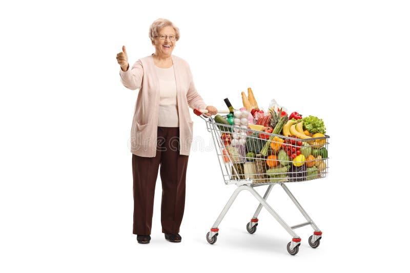 Uśmiechnięta starsza kobieta pozuje z wózkiem na zakupy jedzenie pełno i pokazuje aprobaty obrazy stock