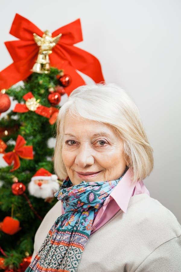 Uśmiechnięta Starsza kobieta Przeciw choince zdjęcie stock