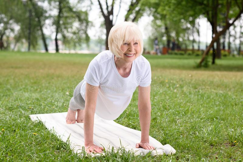 uśmiechnięta starsza kobieta robi desce na joga macie zdjęcie stock