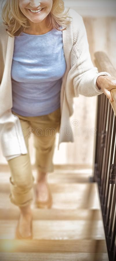 Uśmiechnięta starsza kobieta wspina się na piętrze w domu zdjęcie stock