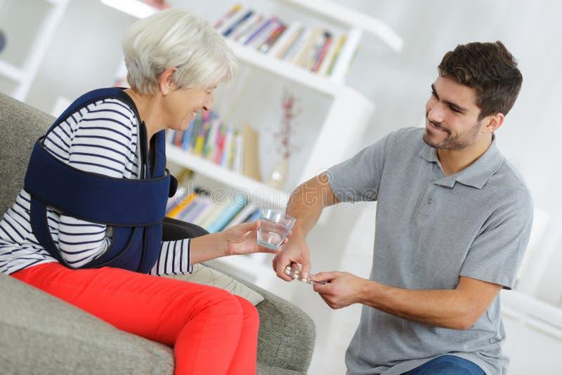 Uśmiechnięta starsza kobieta z młodą męską pielęgniarką obraz stock