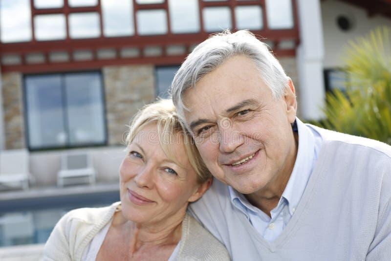 Uśmiechnięta starsza para przed domem fotografia stock