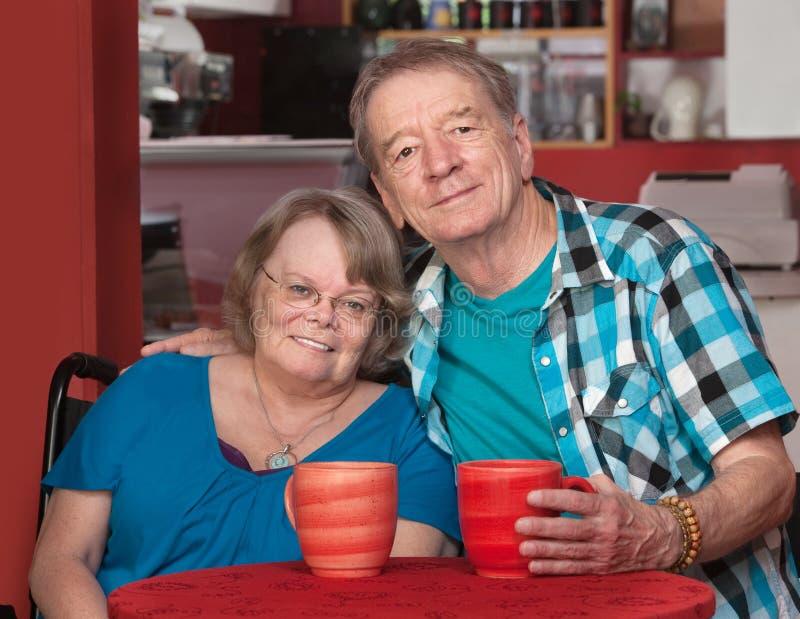 Uśmiechnięta Starsza samiec i kobieta przy stołem zdjęcia stock