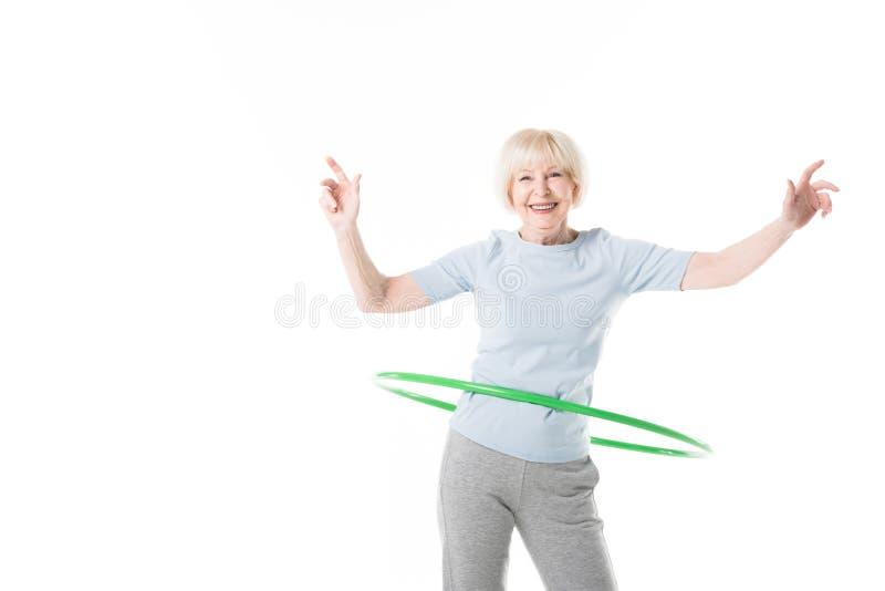 Uśmiechnięta starsza sportsmenka robi hula obręcza ćwiczeniu obraz stock