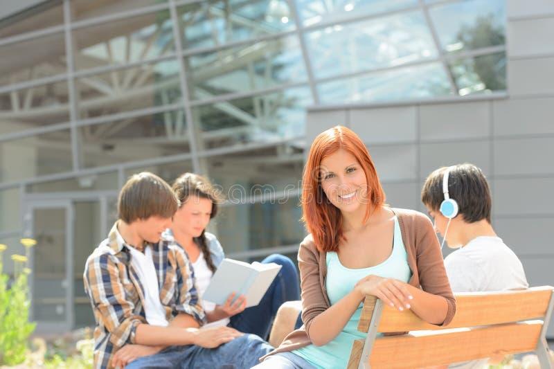 Uśmiechnięta studencka dziewczyna z przyjaciółmi na zewnątrz szkoły wyższa obraz stock