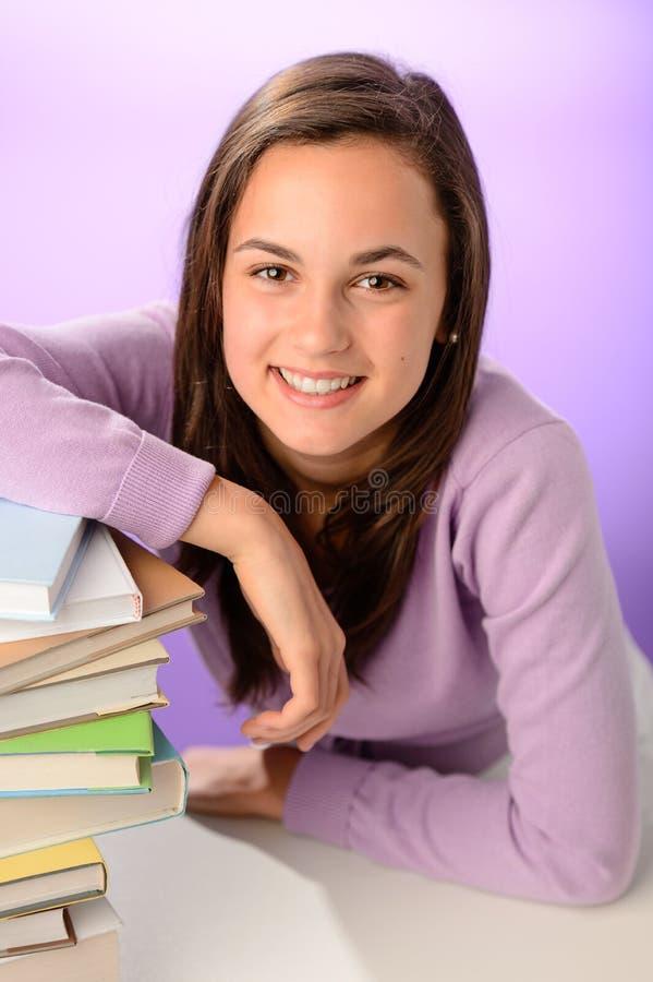 Uśmiechnięta studencka dziewczyna z stosem książki obrazy stock