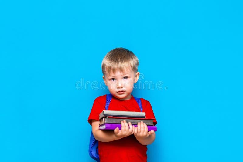 Uśmiechnięta szczęśliwa śliczna mądra chłopiec z plecakiem Dziecko z stosem książki w jego rękach niebieska t?a gotowa do szko?y  obrazy royalty free