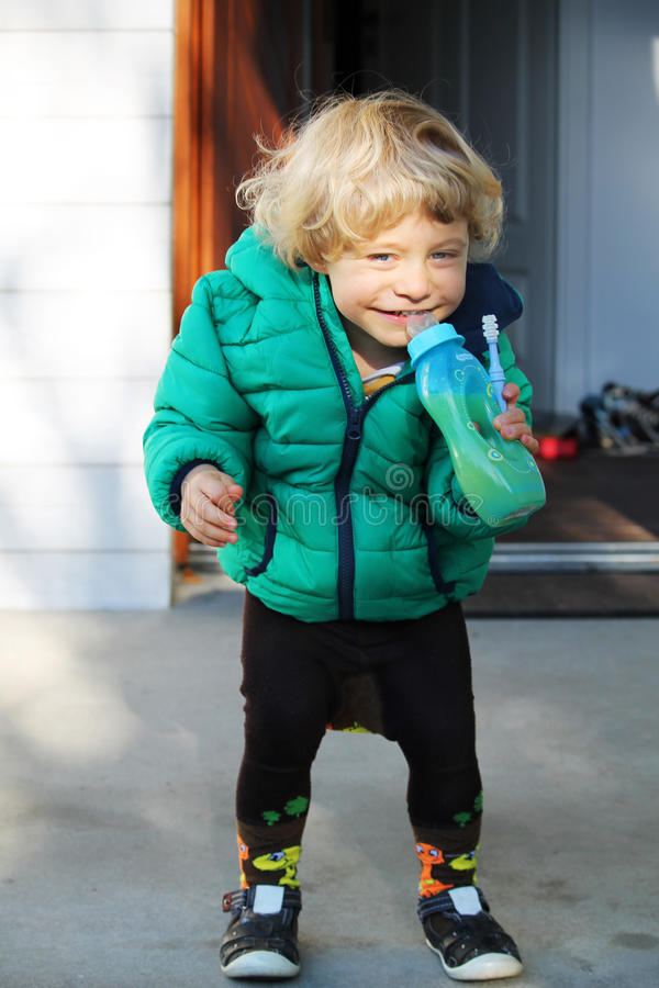 Uśmiechnięta szczęśliwa chłopiec pije sok zdjęcia stock