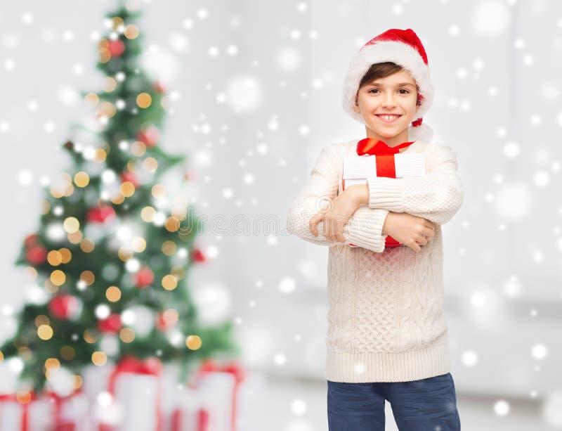Uśmiechnięta szczęśliwa chłopiec w Santa kapeluszu z prezenta pudełkiem obrazy stock