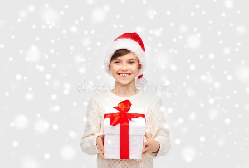 Uśmiechnięta szczęśliwa chłopiec w Santa kapeluszu z prezenta pudełkiem zdjęcie royalty free