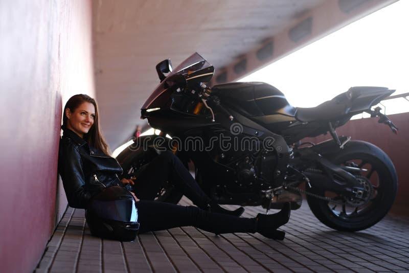 Uśmiechnięta szczęśliwa dziewczyna siedzi w tunelowy pobliskim jej motobike fotografia royalty free