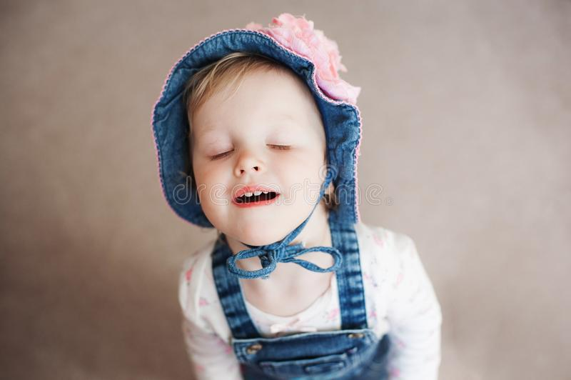 Uśmiechnięta szczęśliwa dziewczynka w lato kapeluszu Panama z dużym menchia kwiatem Spojrzenie przy kamerą zdjęcie stock
