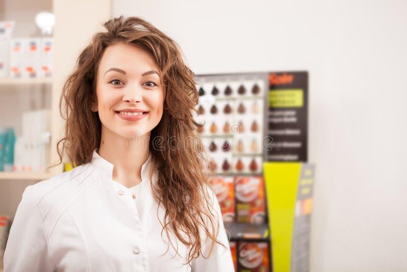 Uśmiechnięta szczęśliwa farmaceuta przed jej biurkiem przy pracą zdjęcia stock