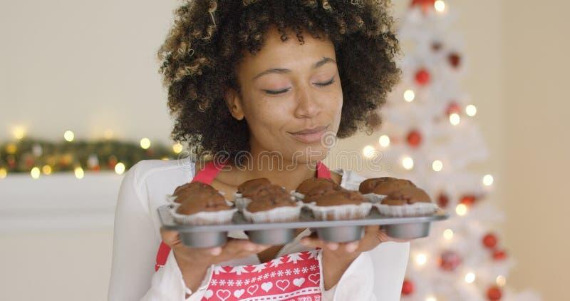 Uśmiechnięta szczęśliwa kobieta z tacą świezi muffins zdjęcie royalty free