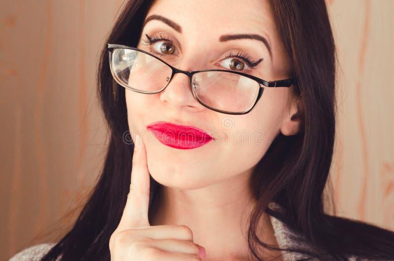 Uśmiechnięta szczęśliwa młoda dziewczyna z szkłami i ciekawym wyrazem twarzy fotografia stock