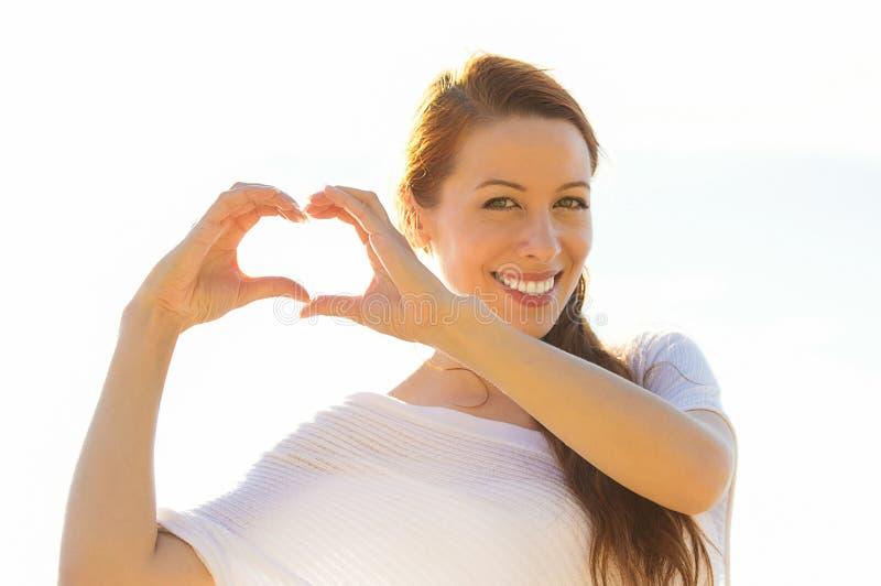 Uśmiechnięta szczęśliwa młoda kobieta robi sercu podpisywać obraz stock