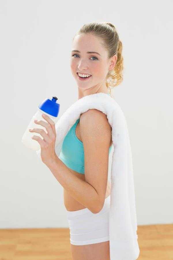 Uśmiechnięta szczupła blondynki pozycja i mienie sportów butelka obrazy stock